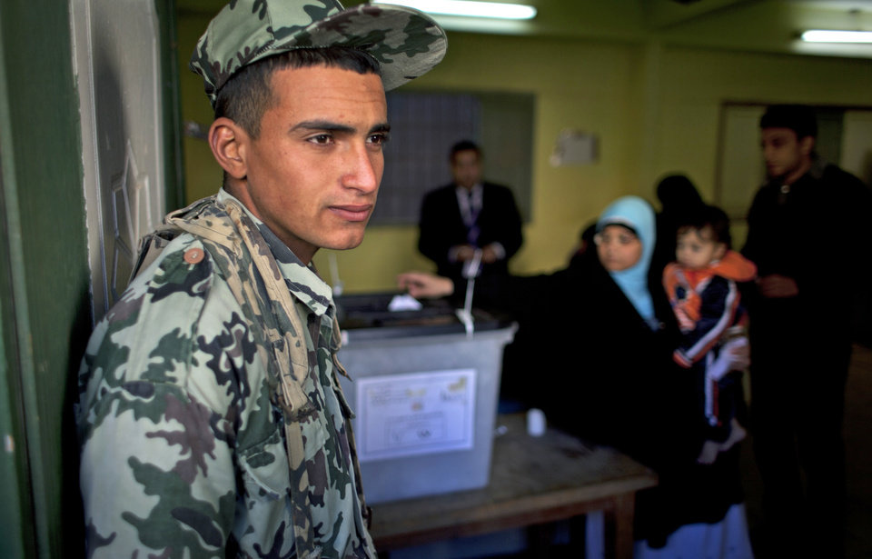 Photo - An Egyptian army soldier guards the site of a polling station as a women casts her vote during the second round of a referendum on a disputed constitution drafted by Islamist supporters of president Mohammed Morsi, in Giza, Egypt, Saturday, Dec. 22, 2012.  Egyptians voted on Saturday in the final phase of a referendum on a proposed new constitution that has polarized the nation, with little indication that the result of the vote will end the political crisis in which the country is mired. (AP Photo/Nasser Nasser)