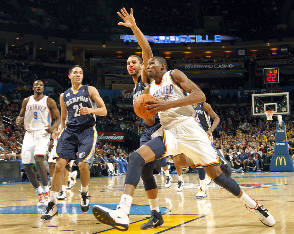 Photo - Kevin Durant (35) drive to the basket past Memphis' Xavier Henry (13) during the NBA basketball game between the Oklahoma City Thunder and the Memphis Grizzlies at the Oklahoma City Arena on Tuesday, Feb. 8, 2011, Oklahoma City, Okla.Photo by Chris Landsberger, The Oklahoman