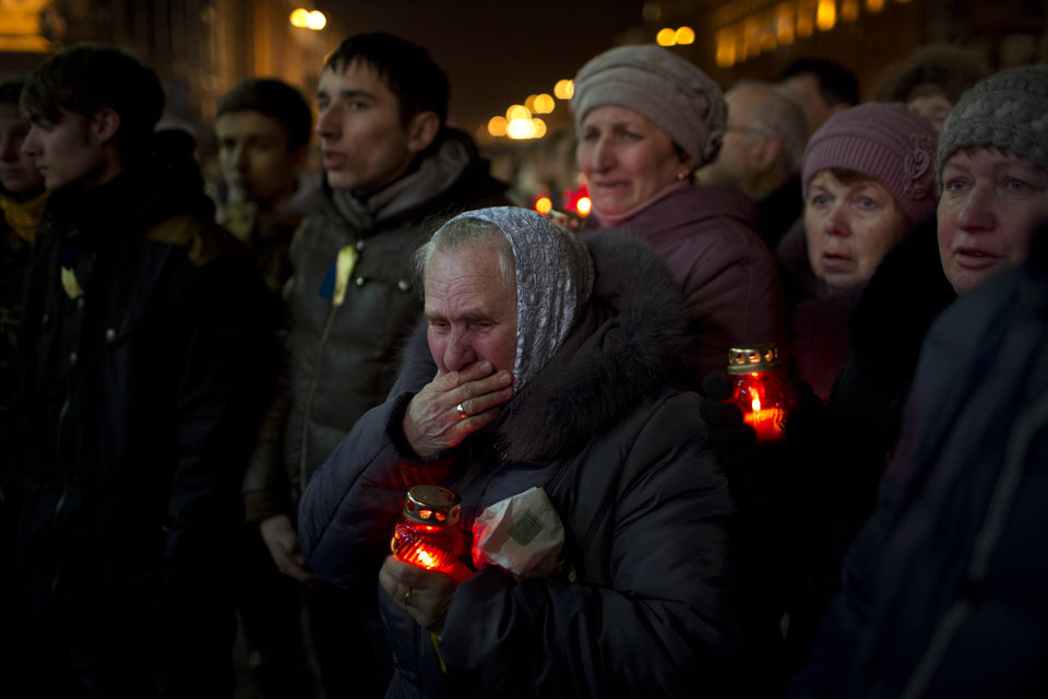 Photo - People react during the funeral of anti-Yanukovych protester Bailuk Alexander, 40, killed in a recent clash with riot police in Kiev's Independence Square, Ukraine, Friday, Feb. 28, 2014. Official reports say 82 people were killed in severe clashes between opposition activists and riot police. (AP Photo/Emilio Morenatti)
