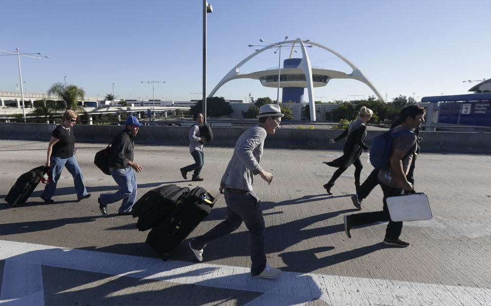 Photo - People run towards Terminal 2 at Los Angeles International Airport on Nov. 1, 2013, after the terminal was reopened. A gunman armed with a semi-automatic rifle opened fire at the airport on Friday, killing a Transportation Security Administration employee and wounding others. (AP Photo/Gregory Bull)