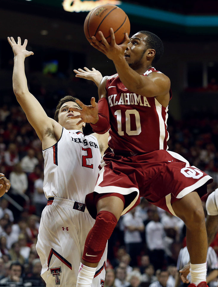 OU�s Jordan Woodard tries to score while being defended by Texas Tech�s Dusty Hannahs during Saturday�s game. Woodard had 15 points and eight assists in the Sooners� 74-65 win. AP Photo