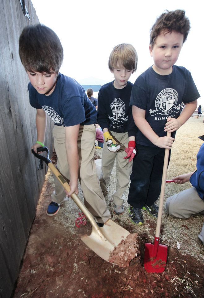 Fourth-grader Jackson Garcia, third-grader Quian Moody and second-grader Matthew Damon turn dirt for a new rain garden at St. Mary's Episcopal Elementary School. PHOTO BY DAVID MCDANIEL, THE OKLAHOMAN. <strong>David McDaniel - The Oklahoman</strong>