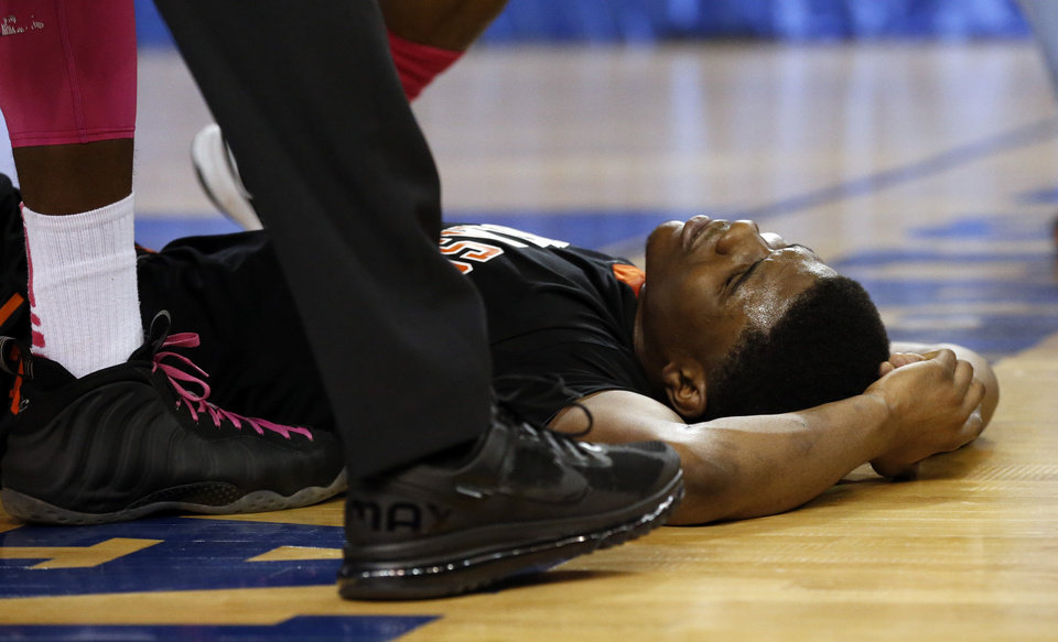 Douglass' Stephen Clark gets attention after a hard fall during the 4a boys championship game where the Douglass high school Trojans play the Roland Rangers at the State Fair Arena on Saturday, March 9, 2013 in Oklahoma City, Okla.  Photo by Steve Sisney, The Oklahoman