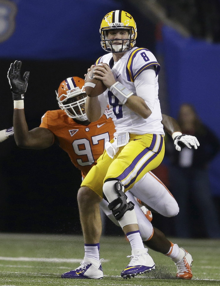 Photo - LSU quarterback Zach Mettenberger (8) prepares to pass the ball under pressure from Clemson defensive end Malliciah Goodman (97) during the first half of the Chick-fil-A Bowl NCAA college football game, Monday, Dec. 31, 2012, in Atlanta. Mettenberger was sacked on the play. (AP Photo/David Goldman)