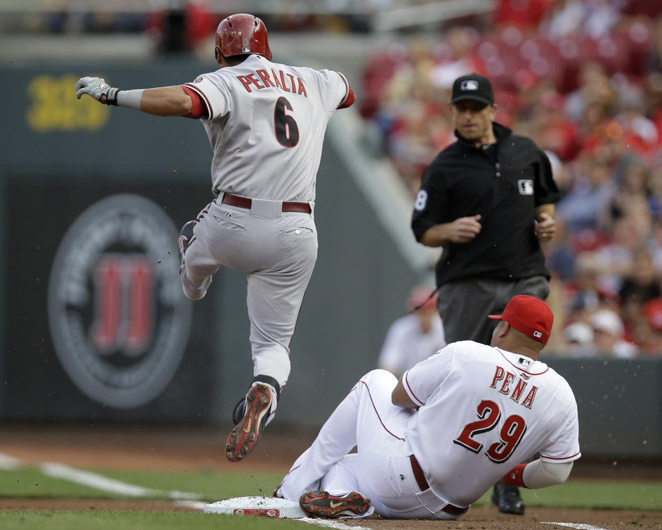 Photo - Arizona Diamondbacks' David Peralta (6) jumps over Cincinnati Reds first baseman Brayan Pena (29) after Pena fielded a ground ball and forced Peralta out at first base in the first inning of a baseball game, Monday, July 28, 2014, in Cincinnati. (AP Photo/Al Behrman)