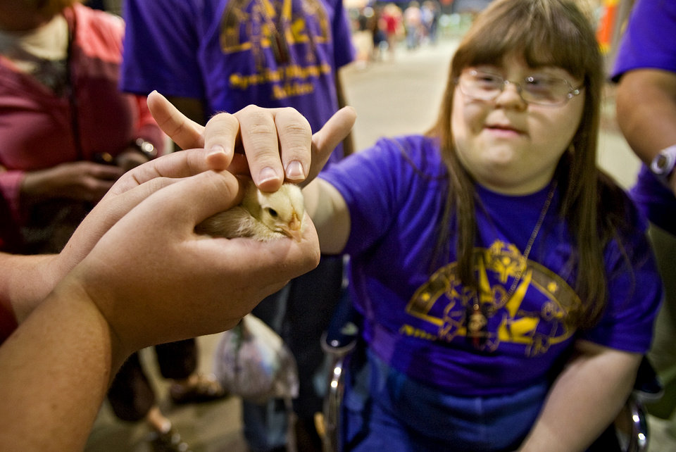 Photo - Courtney Trammel pets a baby chick on her trip to the 2009 Oklahoma State Fair at State Fair Park with the Knights of Columbus on Wednesday, Sept. 23, 2009, in Oklahoma City, Okla.  Photo by Chris Landsberger, The Oklahoman. ORG XMIT: KOD