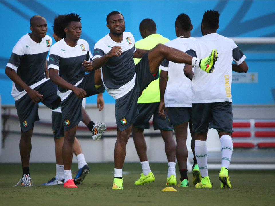Photo - Cameroon soccer players warm up during a training session for the World Cup at the Arena das Dunas in Natal, Brazil, Thursday, June 12, 2014. (AP Photo/Sergei Grits)
