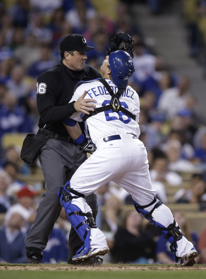 Photo - Los Angeles Dodgers catcher Tim Federowicz, right, collides with umpire Mike DiMuro as Federowicz tries to catch a foul ball hit by Philadelphia Phillies' Freddy Galvis during the fifth inning of a baseball game on Thursday, April 24, 2014, in Los Angeles. Galvis struck out on the at-bat. (AP Photo/Jae C. Hong)