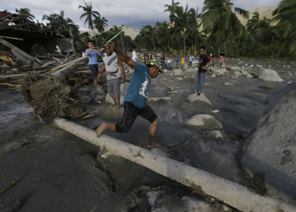 Photo - A resident loses his balance as he looks at the extent of the devastation brought by the flash flood at the height of Typhoon Bopha that hit the village of Andap, New Bataan township, Compostela Valley in southern Philippines Wednesday Dec. 5, 2012. Typhoon Bopha, one of the strongest typhoons to hit the Philippines this year, barreled across the country's south on Tuesday, killing scores of people while triggering landslides, flooding and cutting off power in two entire provinces. (AP Photo/Bullit Marquez)