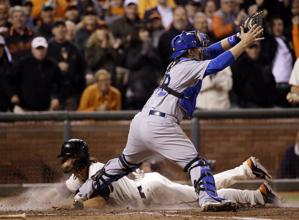 Photo - San Francisco Giants' Angel Pagan, bottom, scores under Los Angeles Dodgers catcher Tim Federowicz, top, after a double by Brandon Belt during the ninth inning of a baseball game on Tuesday, April 15, 2014, in San Francisco. (AP Photo/Marcio Jose Sanchez)