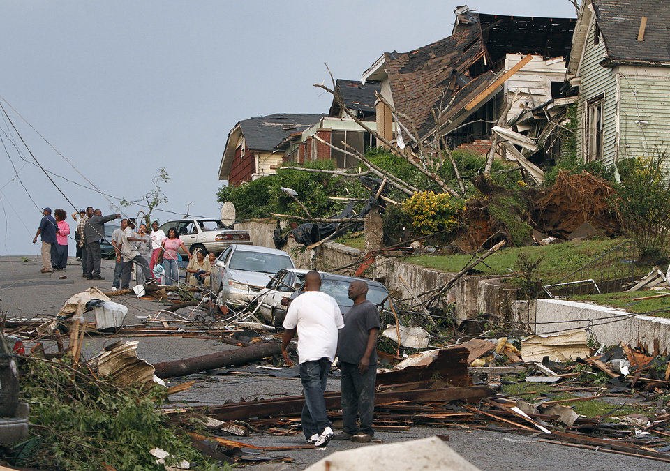 Photo - Residents survey the destruction after a tornado hit Pratt City, Ala. just north of downtown Birmingham, Ala., on Wednesday, April 27, 2011. A wave of severe storms laced with tornadoes strafed the South on Wednesday, killing at least 16 people around the region and splintering buildings across swaths of an Alabama university town. (AP Photo/Butch Dill)