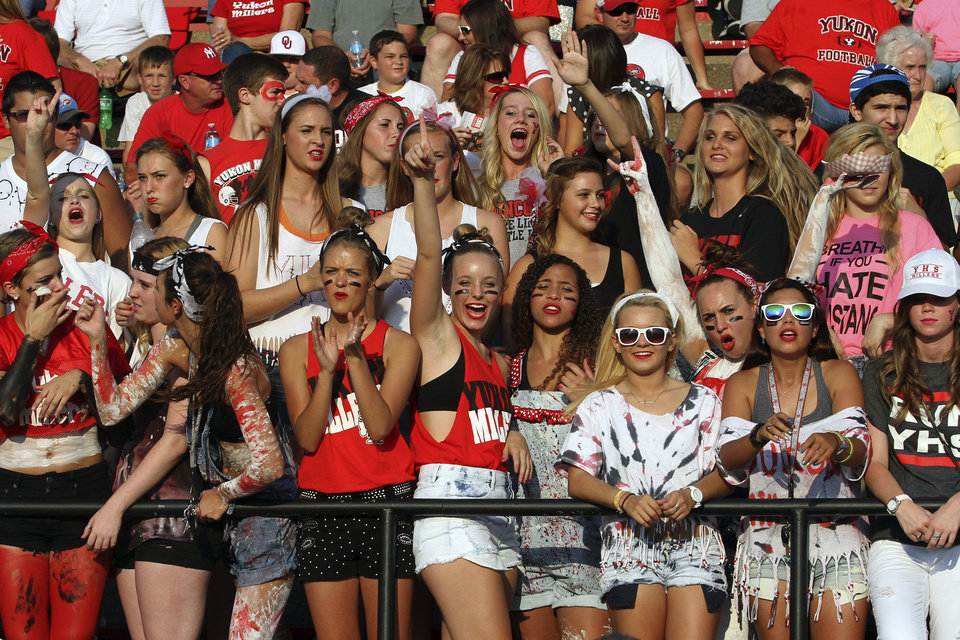Photo - Yukon fans cheer on their team during the Mustang - Yukon High School football  season opener Friday night at Bronco Stadium in Mustang. Photo by Hugh Scott, for the Oklahoman