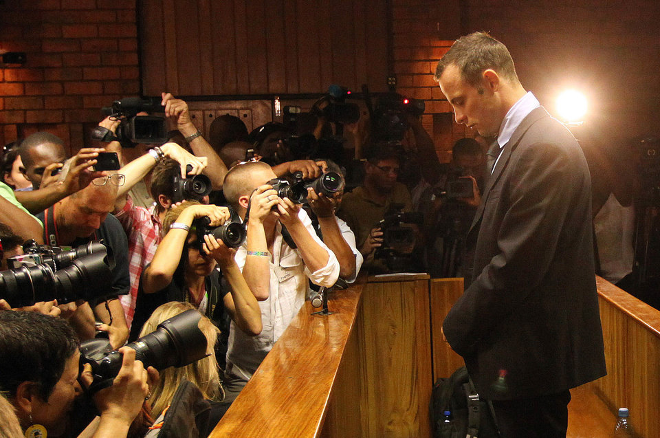 Photo - Photographers take photos of Olympic athlete Oscar Pistorius as he stands in the dock during his bail hearing at the magistrates court in Pretoria, South Africa, Friday, Feb. 22, 2013. The fourth and likely final day of Oscar Pistorius' bail hearing opened on Friday, with the magistrate then to rule if the double-amputee athlete can be freed before trial or if he has to remain in custody over the shooting death of his girlfriend. (AP Photo/Themba Hadebe)