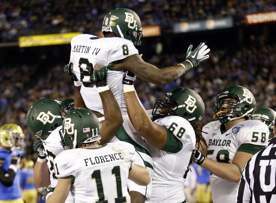 Baylor running back Glasco Martin is lifted by teammates after scoring a touchdown against UCLA during the first half of the NCAA college football Holiday Bowl game, Thursday Dec. 27, 2012, in San Diego. (AP Photo/Lenny Ignelzi)