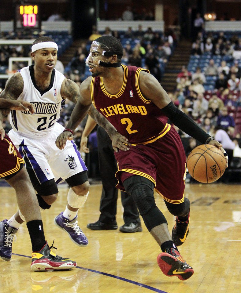 Photo - Cleveland Cavaliers guard Kyrie Irving (2) drives against Sacramento Kings guard Isaiah Thomas during the first quarter of an NBA basketball game in Sacramento, Calif., Monday, Jan. 14, 2013. (AP Photo/Rich Pedroncelli)