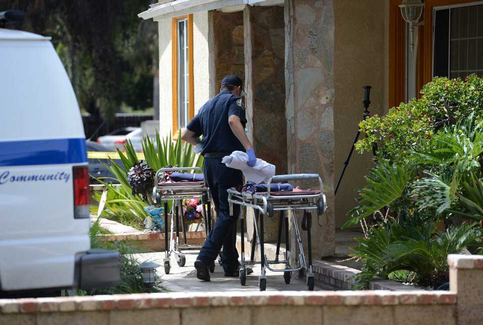 Photo - Pomona Police investigate the scene of a murder-suicide in Pomona, Calif., on Friday, May 9, 2014.  A 28-year-old man shot and killed three members of a Southern California family at the home where they all lived before turning the gun on himself, authorities said Friday. The four bodies were found late Thursday inside the single-story house in a residential area of Pomona, police Lt. Michael Keltner said at a morning news conference.  A woman in her 50s and her 24-year-old daughter and 17-year-old son were killed in their respective bedrooms, he said. (AP Photo/The Inland Valley Daily Bulletin, Jennifer Cappuccio Maher)  MANDATORY CREDIT