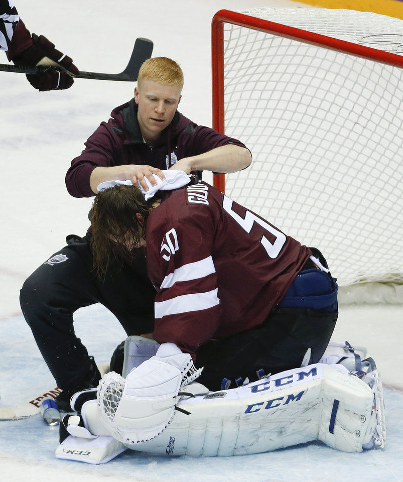 Photo - A trainer treats Latvia goaltender Kristers Gudlevskis after a collision with a Canadian player during the third period of a men's quarterfinal ice hockey game at the 2014 Winter Olympics, Wednesday, Feb. 19, 2014, in Sochi, Russia. Canada won 2-1. (AP Photo/Mark Humphrey)