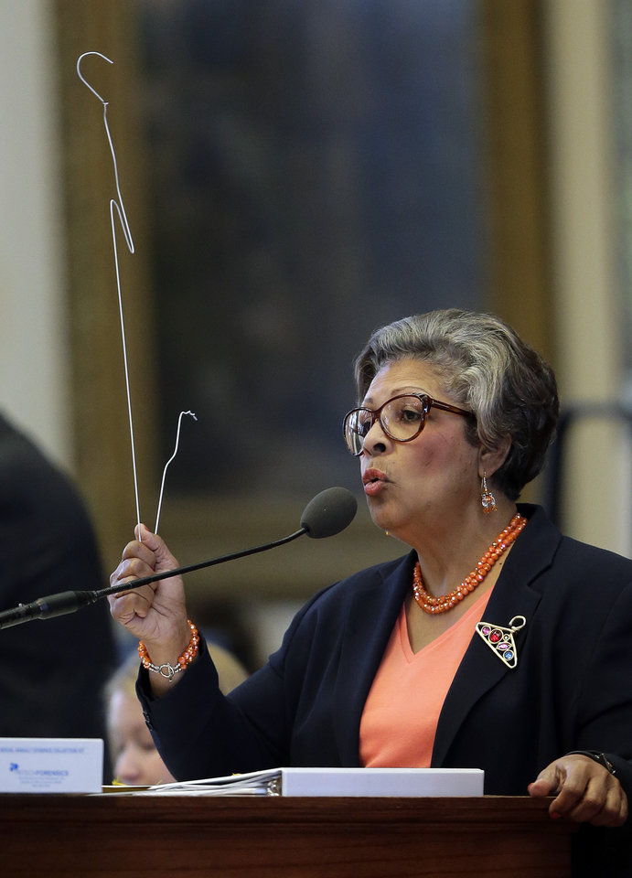 Photo - Rep. Senfronia Thompson, D-Houston, holds a coat hanger as she proposes an amendment to the second reading of HB 2, legislation that will restrict abortion rights, on the Texas House floor,Tuesday, July 9, 2013, in Austin, Texas. The Texas House is expected to vote on the bill Tuesday. (AP Photo/Eric Gay)