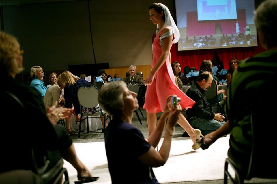 Photo -  Marjorie Maupin (foreground) takes pictures as she and other guests watch models walk down the runway during a fashion show called Insight, a celebration of Culture and Style at National Cowboy and Western Heritage Museum in Oklahoma City on Tuesday, July 19, 2011. The show featured modern styles inspired by traditional Afghan and Rwandan attire. Students from Oklahoma State University designed and created some of the clothing featured in the show. All proceeds from the event benefit The Institute for Economic Empowerment of Women and their program called Peace Through Business. Photo by John Clanton, The Oklahoman