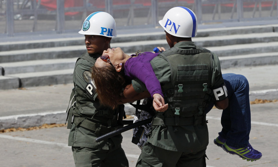 Photo - Military police carry a woman who fainted while waiting in line to see the body of Venezuela's late President Hugo Chavez lying in state at the military academy in Caracas, Thursday, March 7, 2013. While Venezuela remains deeply divided over the country's future, the multitudes weeping and crossing themselves as they reached the president's coffin early Thursday were united in grief and admiration for a man many considered a father figure. (AP Photo/Rodrigo Abd)