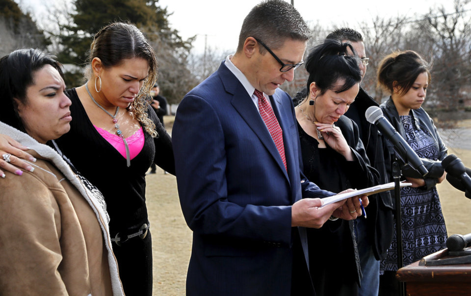 Photo - Attorney Michael Brooks-JimÂŽnez, center,  reads a statement before releasing the cell phone video taken on Feb. 15  in the parking lot of a Moore movie theatre where Luis Rodriguez  died after being handcuffed by police officers.  The  video was recorded by Rodriguez's wife, Nair, shown in this photo to the right of Brooks-Jiminez.  Others in photo are family members. The news conference was held in front of Northwest Free Will Baptist Church, 4625 NW 36 on Tuesday morning, Feb. 25, 2014.     Photo by Jim Beckel, The Oklahoman