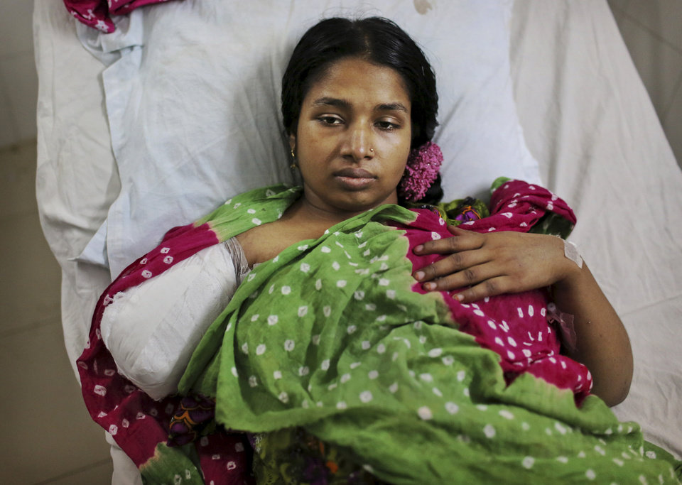 Photo - A Bangladeshi garment worker who was rescued from a building that collapsed Wednesday lays in a hospital bed with an amputated arm sustained when she was trapped inside, in Savar, near Dhaka, Bangladesh, Sunday, April 28, 2013. A fire broke out late Sunday in the wreckage of the garment factory that collapsed last week in Bangladesh killing hundreds, with smoke pouring from the piles of shattered concrete and some of the rescue efforts forced to stop.(AP Photo/Kevin Frayer)