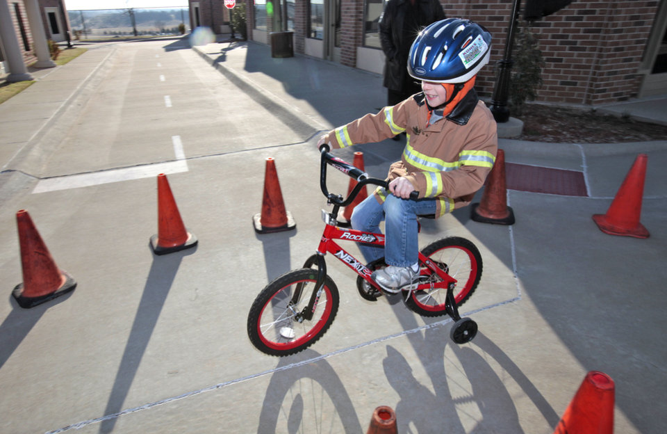 Zachery Duck, 7, rides a bicycle through a safety course during Edmond Fire Department's Children's Safety Challenge over spring break. PHOTO BY DAVID MCDANIEL, THE OKLAHOMAN. <strong>David McDaniel - The Oklahoman</strong>