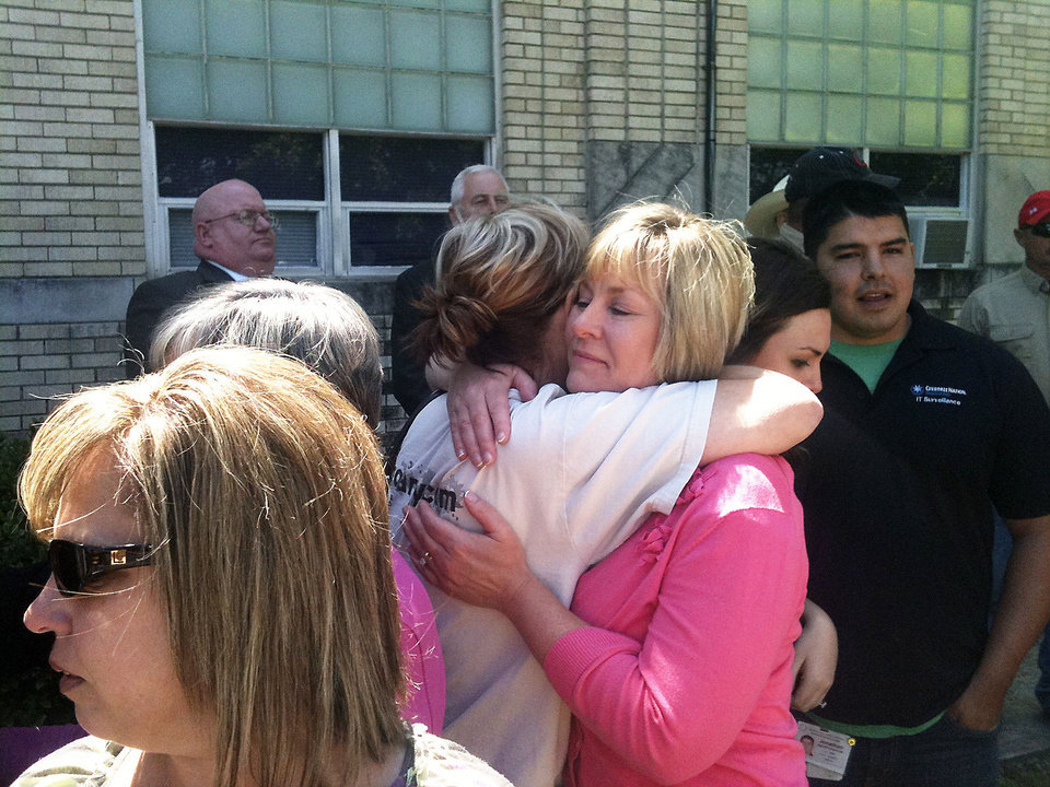 Kim Stout, at right in pink shirt, hugs another woman after a news conference announcing an arrest in her father's killing. Leo Boyd Reasnor, Stout's father, was killed in June 1987 by a gunshot wound to the head.  PHOTO BY ANDREW KNITTLE, THE OKLAHOMAN