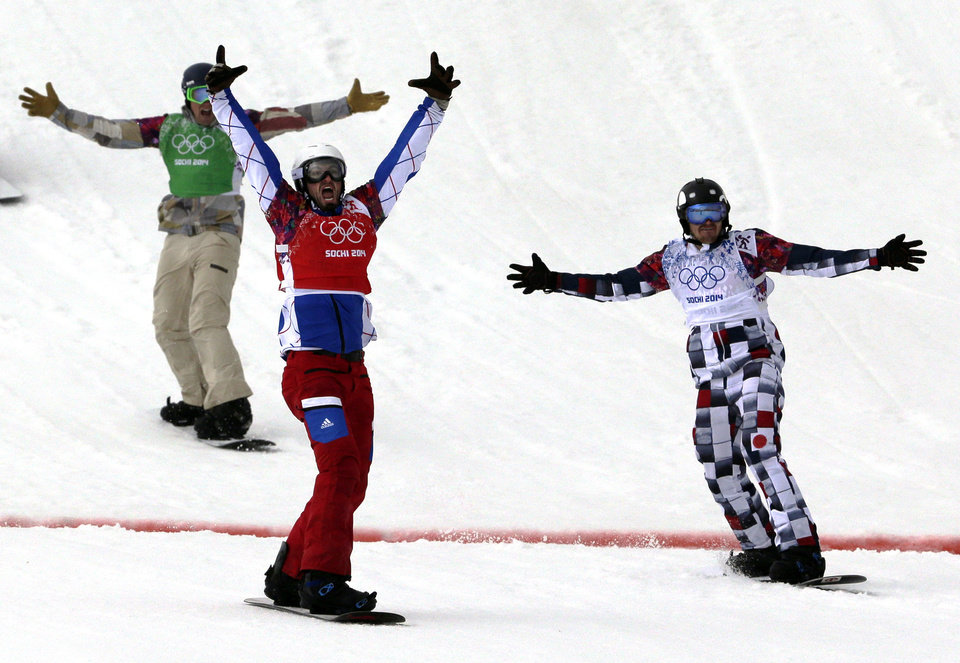 Photo - France's Pierre Vaultier, second left, celebrates taking the gold medal ahead of silver medalist Nikolai Olyunin of Russia, right, and bronze medalist Alex Deibold of the United States in the men's snowboard cross final at the Rosa Khutor Extreme Park, at the 2014 Winter Olympics, Tuesday, Feb. 18, 2014, in Krasnaya Polyana, Russia. (AP Photo/Andy Wong)