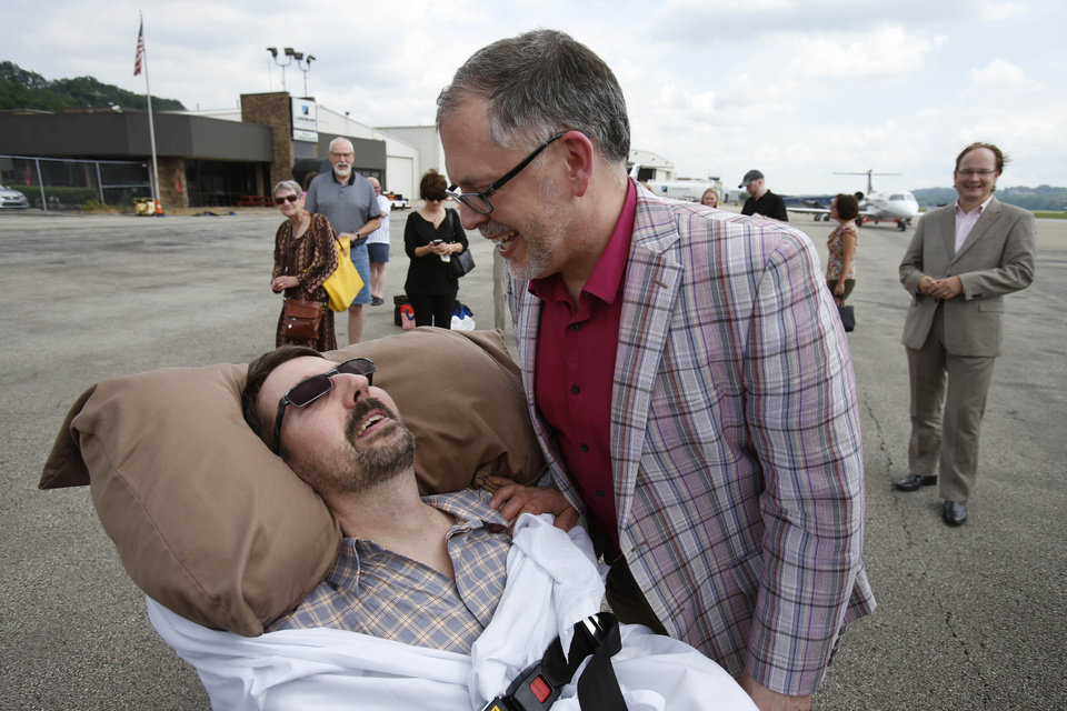 Photo - This photo made Thursday, July 11, 2013, shows Jim Obergefell, right, and John Arthur after they returned from their wedding flight at Landmark Aviation at Cincinnati's Lunken Airport. The couple were married during a short ceremony on the plane, on the tarmac, at Baltimore/Washington International Thurgood Marshall Airport, after flying in from Cincinnati.  John suffers from ALS, is bed-ridden, and is now in hospice care. A federal judge has ruled in favor of the two Ohio men who want their out-of-state marriage recognized John nears death, a case that's seen as encouraging for same-sex marriage supporters in Ohio. (AP Photo/The Cincinnati Enquirer, Gary Landers) MANDATORY CREDIT, NO SALES