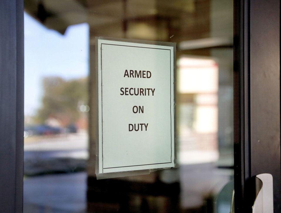 Photo - A notice posted on the school's front doors advises visitors that Council Grove Elementary School has an armed security officer on duty on the premises.  Living in a high crime zone in west Oklahoma City that is now benefitting from increased police patrols funded by a Safe Oklahoma grant from the state attorney general.   Photo taken  Wednesday , Nov. 13, 2013. Photo by Jim Beckel, The Oklahoman  Jim Beckel - THE OKLAHOMAN