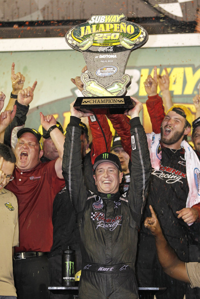 Kurt Busch celebrates with the winner's trophy after winning the Nationwide Series NASCAR auto race at Daytona International Speedway, Friday, July 6, 2012, in Daytona Beach, Fla. (AP Photo/Terry Renna)