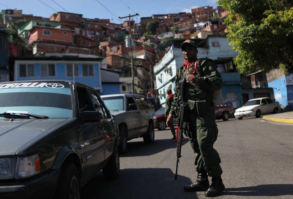 A member of the Bolivarian militia, a militia created by President Hugo Chavez estimated to number more than 100,000 who do not report to the armed forces, stands at a checkpoint in the 23 de Enero neighborhood of Caracas, Venezuela, Saturday, Oct. 6, 2012. Chavez is running for re-election against opposition candidate Henrique Capriles in Sunday's presidential election. (AP Photo/Rodrigo Abd)
