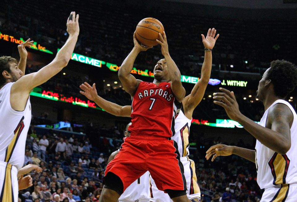 Photo - Toronto Raptors guard Kyle Lowry (7) drives to the basket against New Orleans Pelicans center Jeff Withey, left, and New Orleans Pelicans forward Al-Farouq Aminu, right, during the first half of an NBA basketball game in New Orleans, Wednesday, March 19, 2014. The Raptors won 107-100. (AP Photo/Jonathan Bachman)