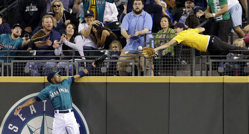 Photo - A fan reaches for a home run by Washington Nationals' Bryce Harper as Seattle Mariners center fielder Austin Jackson stretches for it in the eighth inning of a baseball game Friday, Aug. 29, 2014, in Seattle. (AP Photo/Elaine Thompson)