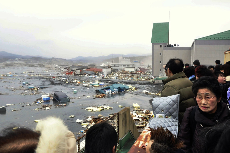 Photo - People watch the aftermath of tsunami tidal waves covering a port at Kesennuma in Miyagi Prefecture, northern Japan, after strong earthquakes hit the area Friday, March 11, 2011. (AP Photo/Keichi Nakane, The Yomiuri Shimbun)  JAPAN OUT, CREDIT MANDATORY ORG XMIT: TOK826