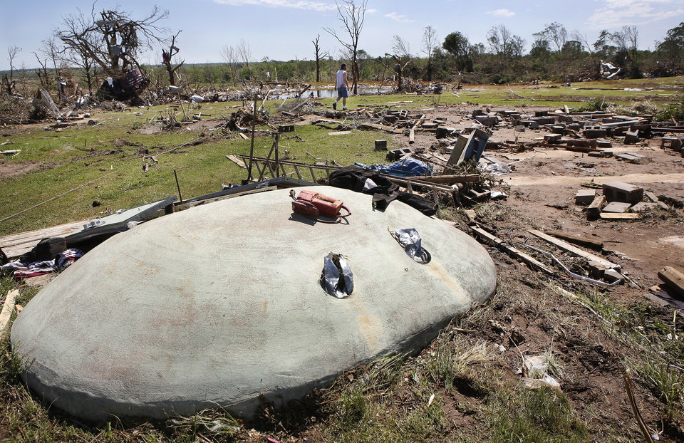 Photo - Bill Stoops, seen walking on his property in the background, sought safety along with three other adults and four children from a tornado that destroyed his home and many other houses in Steelman Estates in Bethel Acres on Sunday, May 19, 2013. His double-wide manufactured home used to be on the empty spot to the right of the shelter.  Jim Beckel - THE OKLAHOMAN
