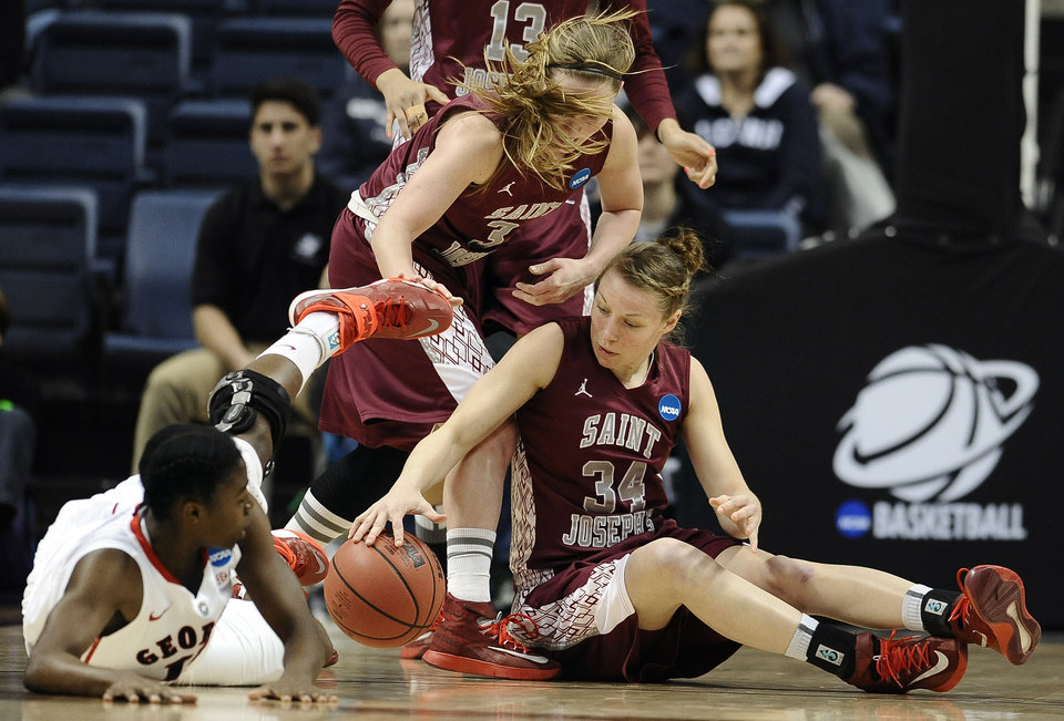 Photo - Saint Joseph's Erin Shields, center, and Kelsey Berger, right, fight with with Georgia's Krista Donald, left, for possession of the ball during the first half of a first-round game of the NCAA women's college basketball tournament, Sunday, March 23, 2014, in Storrs, Conn. (AP Photo/Jessica Hill)