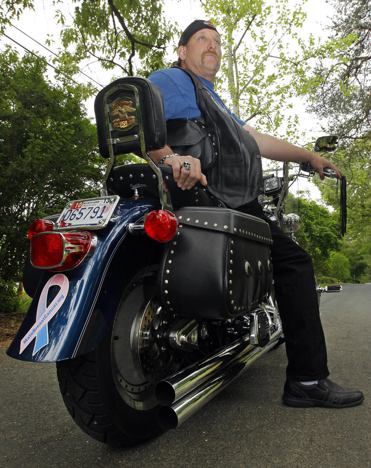 Photo -   In this May 3, 2012 photo, breast cancer survivor Robert Kaitz sits on his motorcycle, which displays a male breast cancer survivor ribbon, in Severna Park, Md. Kaitz thought a small growth under his left nipple was just a harmless cyst. By the time he had it checked out in 2006, almost two years later, the lump had started to hurt. The diagnosis of breast cancer was a shock.