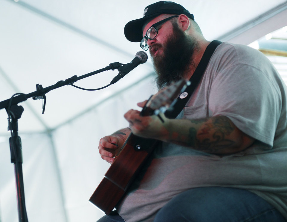 Photo - Oklahoma artist John Moreland performs at OKC Fest in downtown Oklahoma City on Friday, June 27, 2014. OKC Fest is a new two day country music festival with multiple stages downtown. Photos by KT King/The Oklahoman