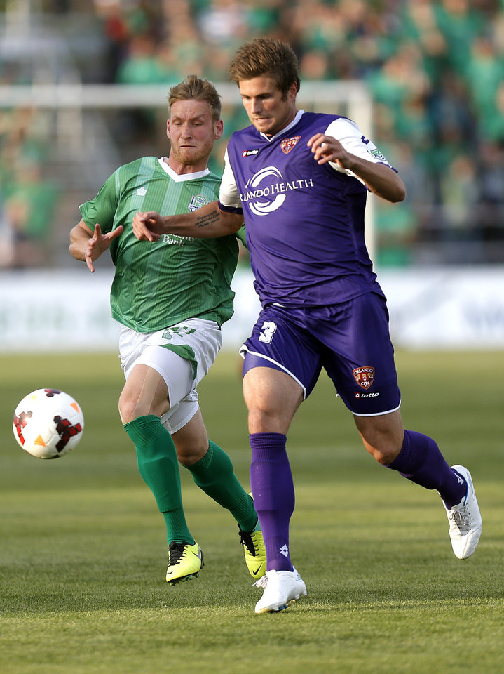 Photo - Oklahoma City's Kyle Greig and Orlando City's Brad Rusin chase down a ball from during the OKC Energy FC soccer game against Orlando City SC at Pribil Stadium in Oklahoma City, Saturday, April 26, 2014. Photo by Sarah Phipps, The Oklahoman