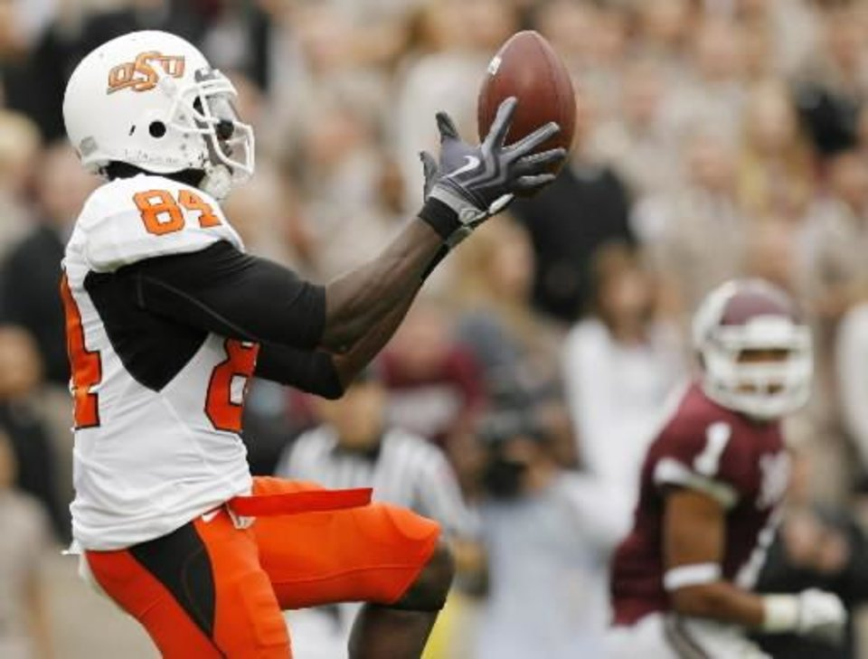 Photo - OSU's  Hubert  Anyiam (84) catches a tipped pass for a touchdown in the second quarter during the college football game between Oklahoma State University (OSU) and Texas A&M University at Kyle Field in College Station, Texas, Saturday, October 10, 2009. Trent Hunter (1) of Texas A&M is in the background. Photo by Nate Billings