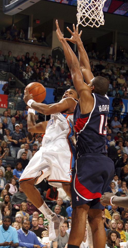 Photo - Oklahoma City's Earl Watson (25) shoots a layup over Atlanta's Al Horford (15) during the second half of the NBA game between Oklahoma City Thunder and the Atlanta Hawks, Sunday, Nov. 9, 2008, at  the Ford Center, Oklahoma City. PHOTO BY SARAH PHIPPS, THE OKLAHOMAN
