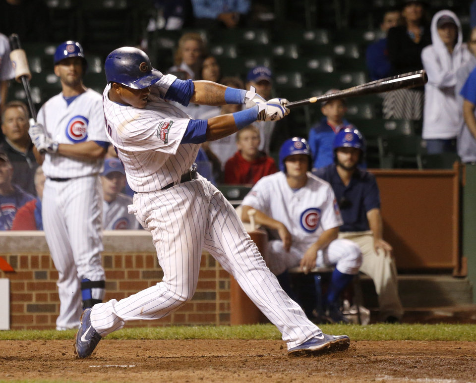 Photo - Chicago Cubs' Starlin Castro hits a game winning sacrifice fly off a pitch from Colorado Rockies relief pitcher Tyler Matzek, scoring John Baker, during the 16th inning of a baseball game Wednesday, July 30, 2014, in Chicago. The Cubs' won 4-3. (AP Photo/Charles Rex Arbogast)