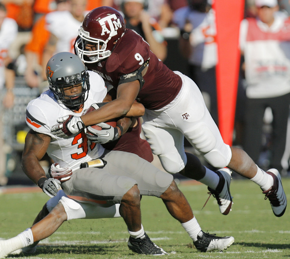 Texas A&M's Charlie Thomas (9) and Trent Hunter (1) bring down Oklahoma State's Jeremy Smith in the second half of the Cowboys' win on Saturday. Photo by Nate Billings, The Oklahoman