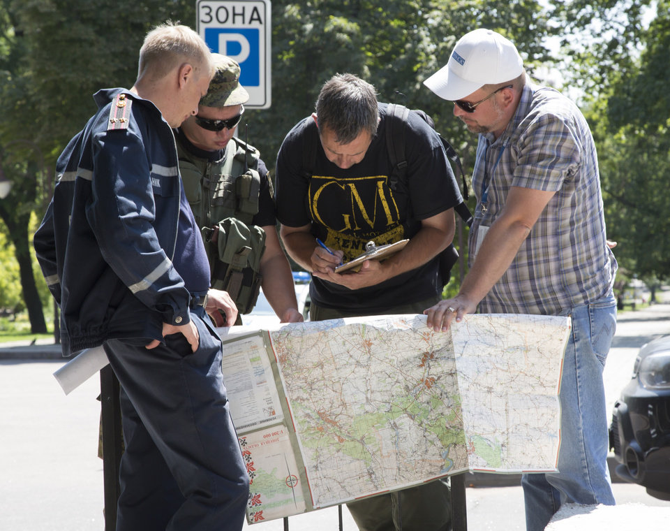 Photo - Ukrainian Ministry Emergency officer, left, Donetsk People's Republic fighter, 2nd left, and members of the OSCE mission in Ukraine examine a map as they discuss the situation around the site of the crashed Malaysia Airlines Flight 17 in the city of Donetsk, eastern Ukraine Sunday, July 27, 2014. A team of international police officers that had been due to visit the site of the Malaysian plane disaster in eastern Ukraine cancelled the trip Sunday after receiving reports of fighting in the area. Alexander Hug, the deputy head of a monitoring team from the OSCE in Europe, said it would be too dangerous for the unarmed mission to travel to the site from its current location in the rebel-held city of Donetsk. (AP Photo/Dmitry Lovetsky)