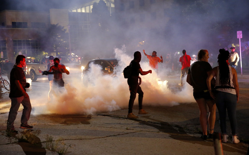 Photo - People walk in front of the Oklahoma City Police Department as a tear gas cloud goes in the air in Oklahoma City, Saturday, May 30, 2020. The protest was in response to the death of George Floyd. [Sarah Phipps/The Oklahoman]