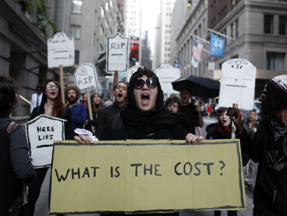 Photo -   Protestors chant during an Occupy Wall Street march, Monday, Sept. 17, 2012, in New York. A handful of Occupy Wall Street protestors were arrested during a march on the New York Stock Exchange on the anniversary of the grass-roots movement. (AP Photo/Jason DeCrow)