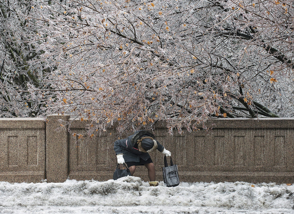 Photo - A pedestrian ducks under a frozen tree on S.Clair Ave. in Toronto after an ice storm caused havoc and cut power to much of the city on Sunday, Dec. 22, 2013. (AP Photo/The Canadian Press, Aaron Vincent Elkaim)