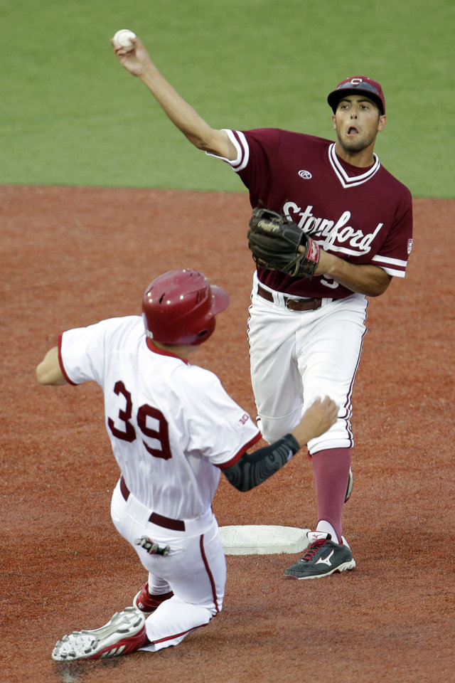 Photo - Stanford's Brett Michael Doran, right, throws to first for a double play after tagging the base to out Indiana's Craig Dedelow (39) during an NCAA college baseball regional tournament game in Bloomington, Ind.,  Monday, June 2, 2014. (AP Photo/AJ Mast)